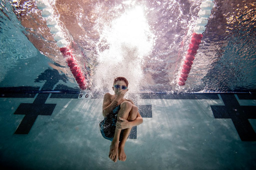 Child jumping into pool with goggles holding nose in Portland Oregon