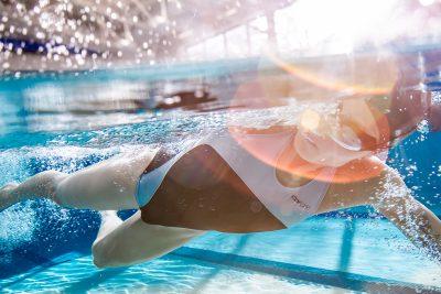 Swimmer racing toward finish line. Underwater photo. Ray of light.
