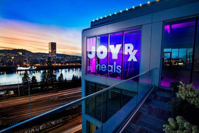A beautiful colorful sunset photo of a building with the Childrens Cancer Association new sign called JoyRX on 7 SE Stark in Portland, Oregon