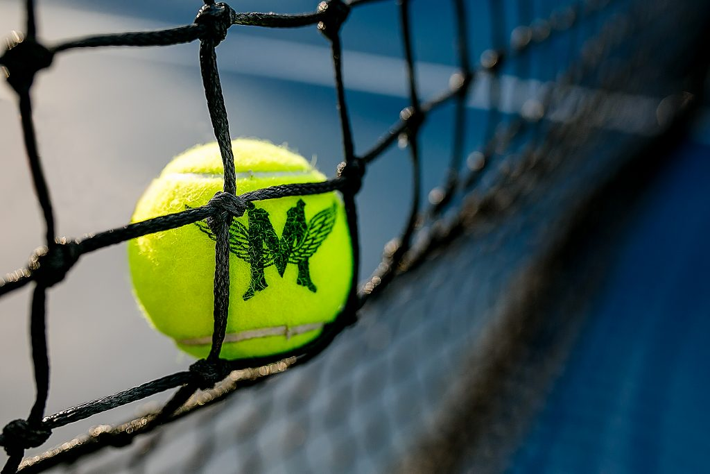 Detail photo of tennis ball flying against net at Multnomah Athletic Club in Portland