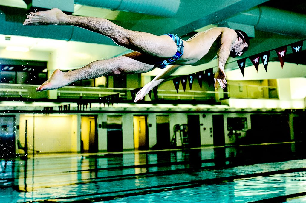 Swimmer diving into pool for racing at Multnomah Athletic Club in Portland Oregon