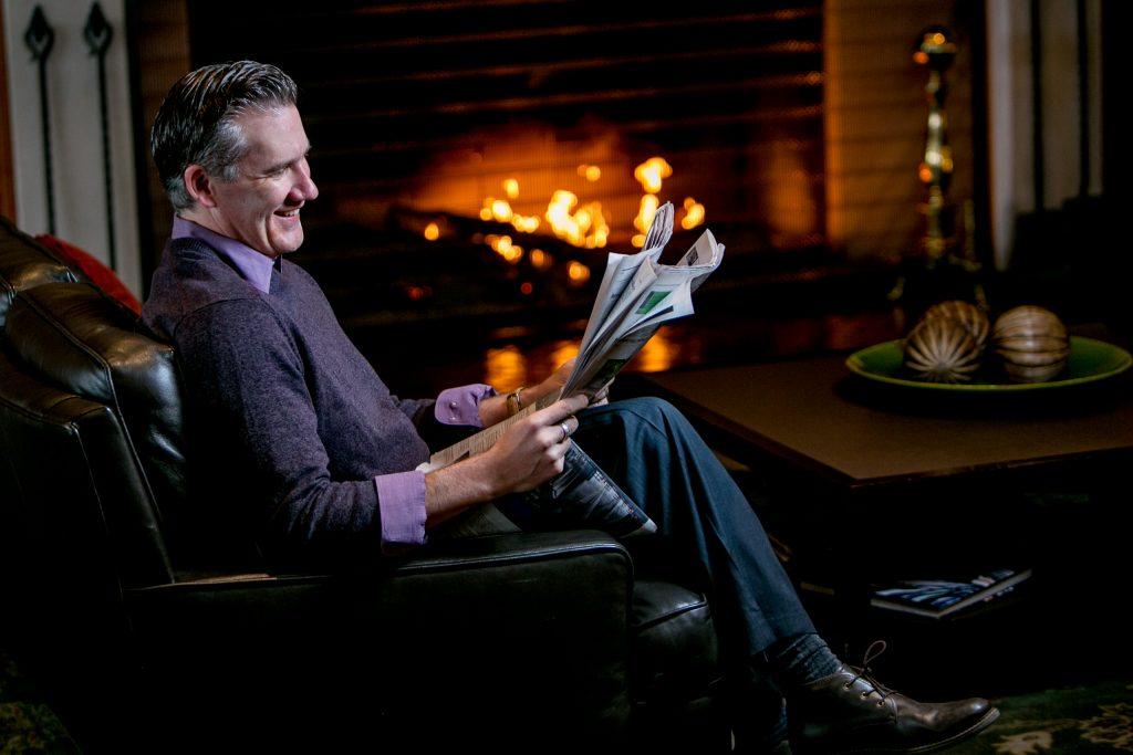 Man enjoying reading near fire at Multnomah Athletic Club in Portland