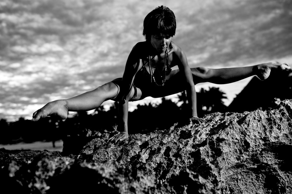 Woman doing yoga splits on sharp rocks in Mayatulum Spa and Resort