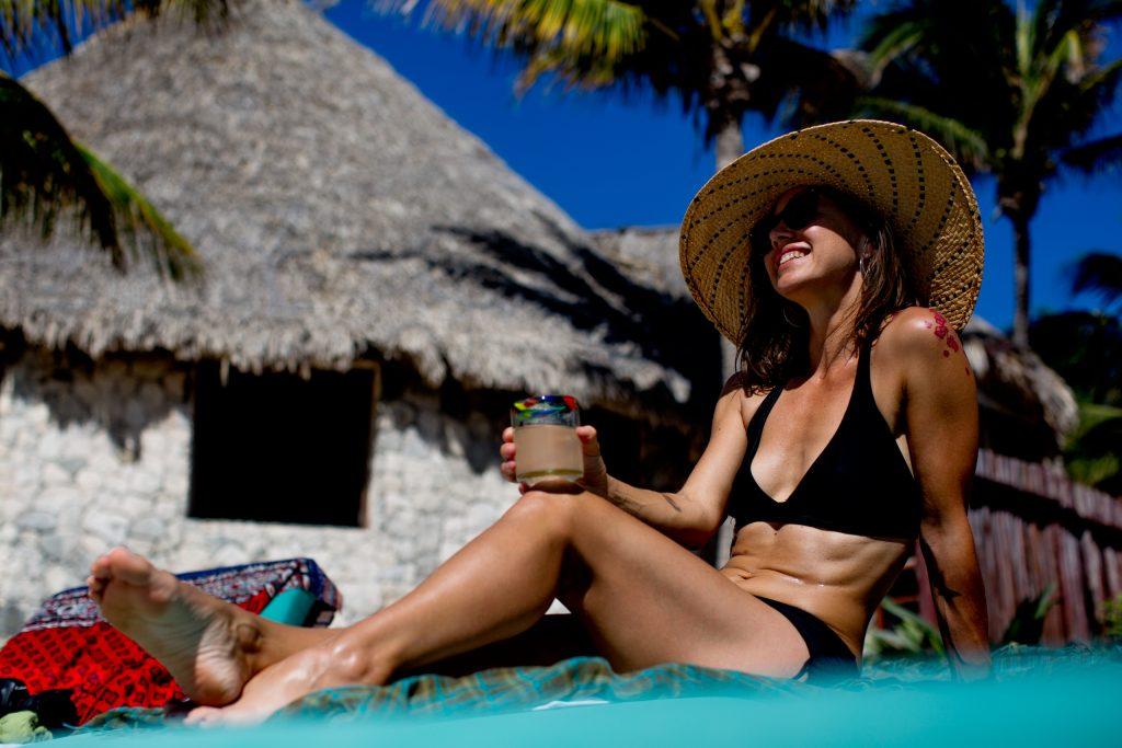 Woman sunbathing with big hat in Mayatulum Mexico