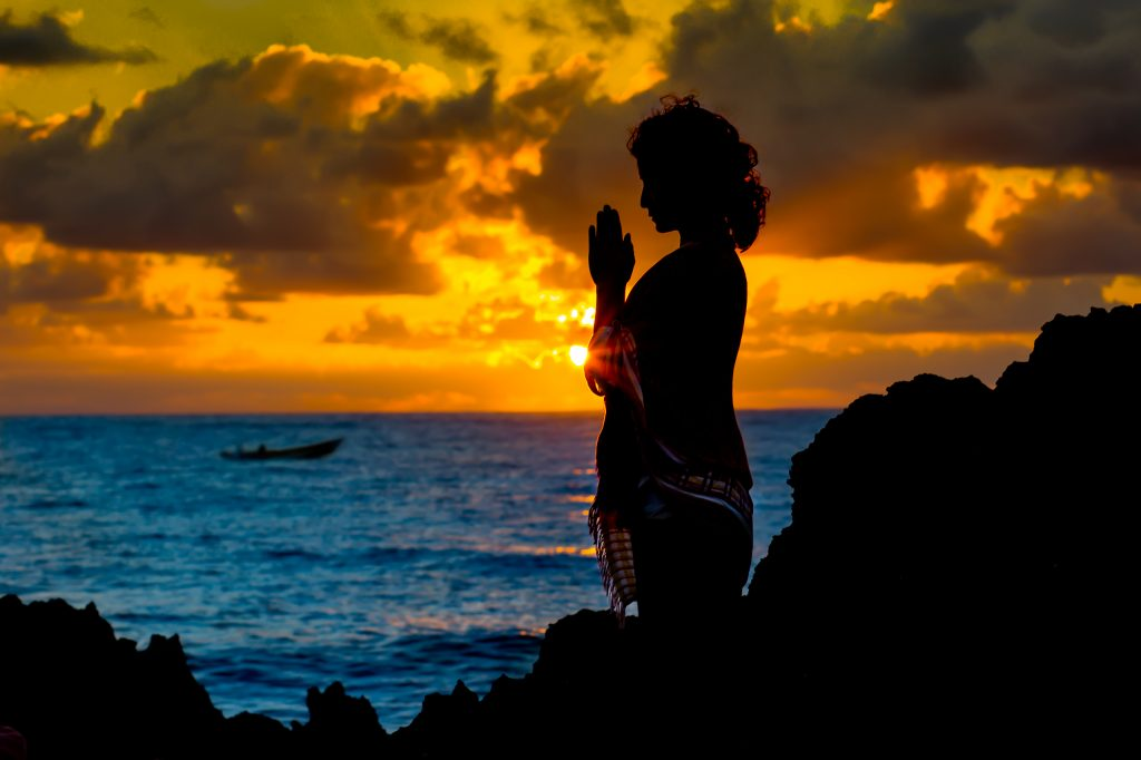 Woman silhouetted against early morning sunrise in meditation