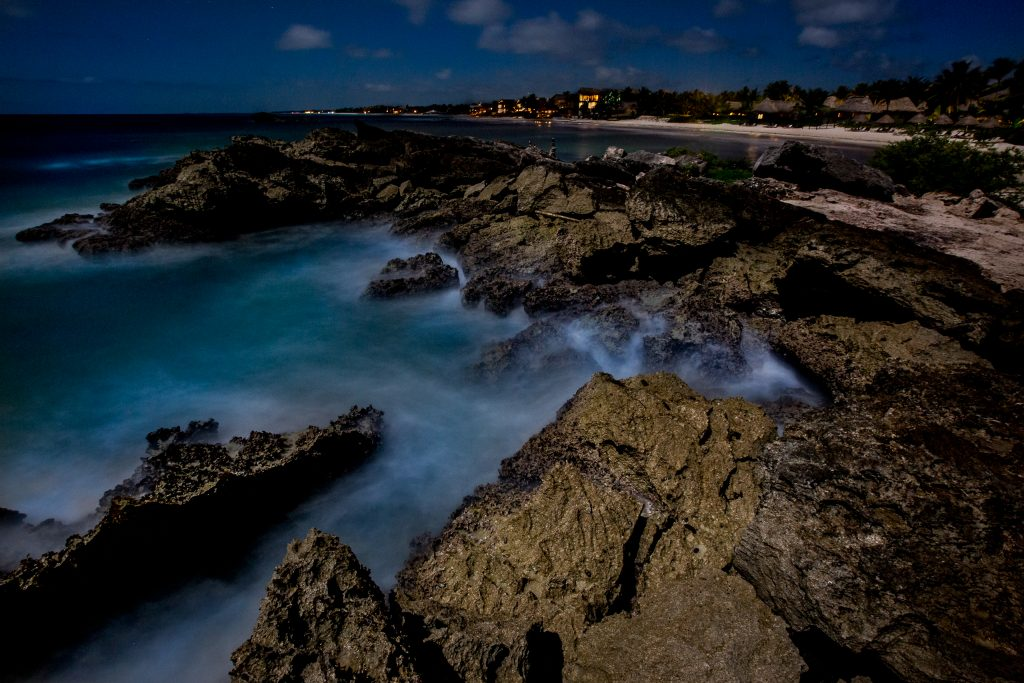 Long exposure of ocean waves crashing over rocks in Mayatulum Mexico