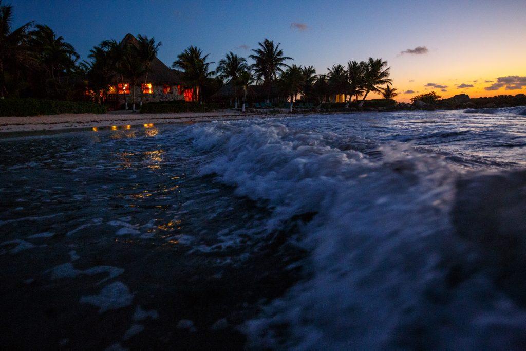 Long exposure of ocean waves crashing over rocks in Mayatulum Mexico