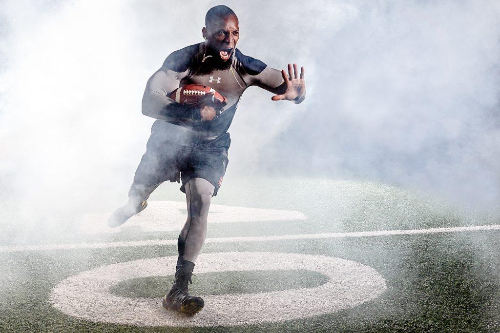 Ahman Green football player bursting through fog on field