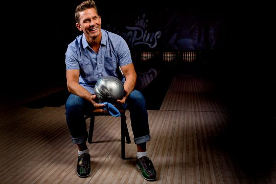 Good looking guy cleaning bowling ball at Kingpins alley in Portland Oregon