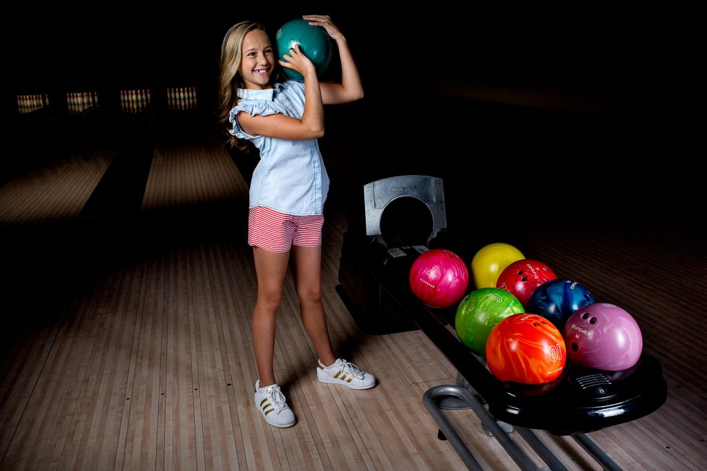 Cute girl holding bowling ball at Kingpins in Portland Oregon