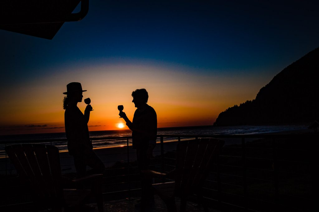Silhouette of 2 people drinking wine at sunset at the beach