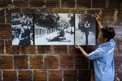 Woman hanging photography wall art on wall